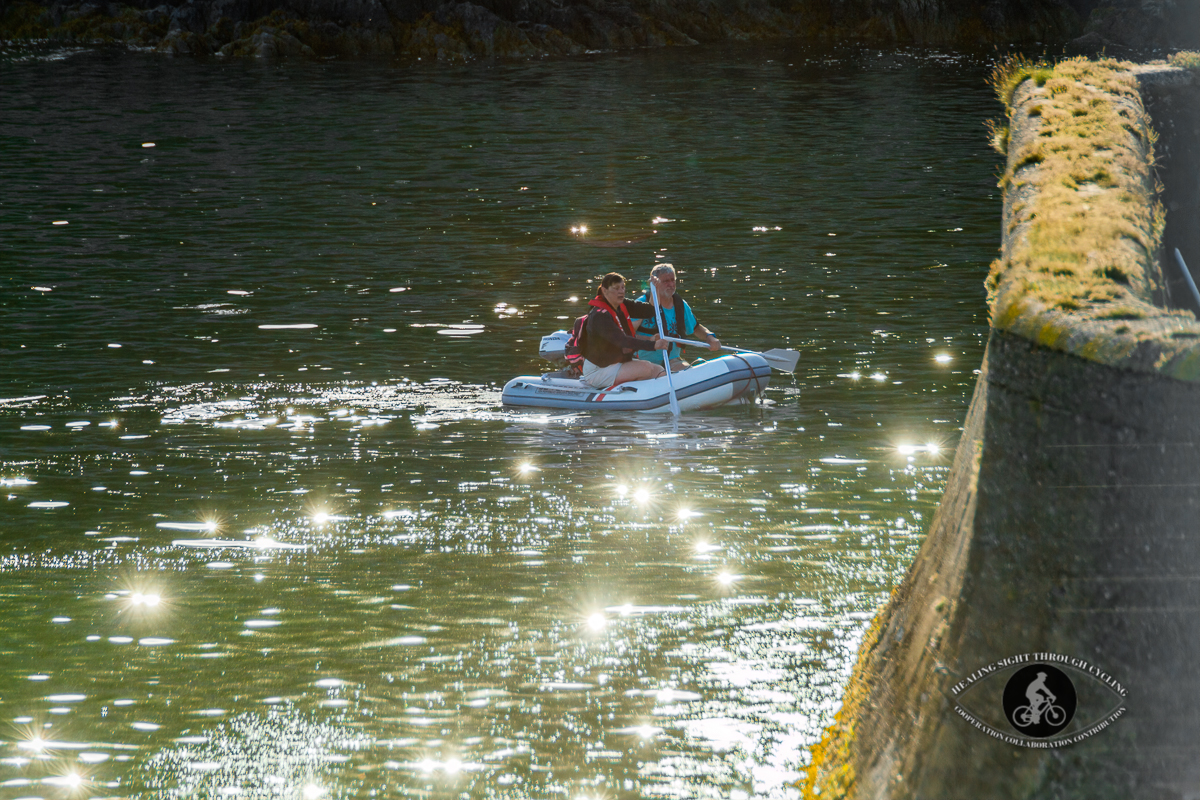 Couple in a dinghy in Glandore Bay sun sparkles on the water - County Cork