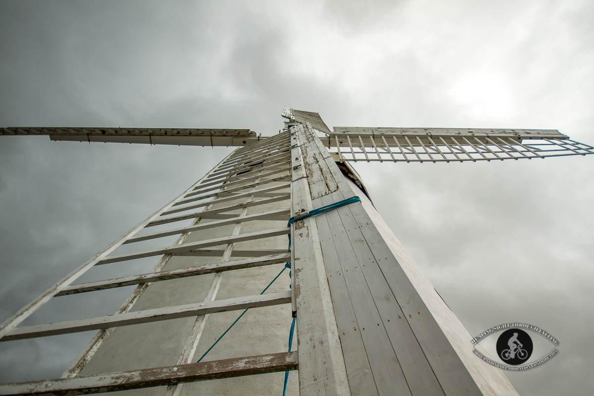 Blennerville Windmill looking up at blades from exterior under stormy clouds - wider lens