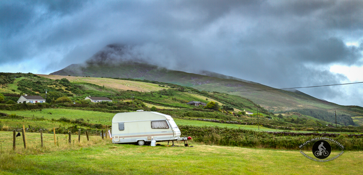 Caravan in front of stormy clouds on mountain - panorama