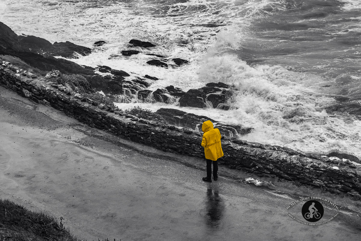 Man on road with waves in the Wild Atlantic Way near Dingle - BW Selective colour