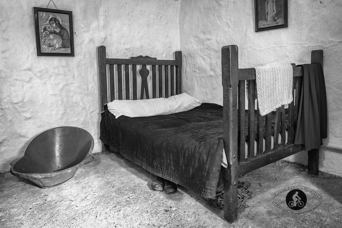 Room and bed inside old building in Bunratty Castle Village - BW