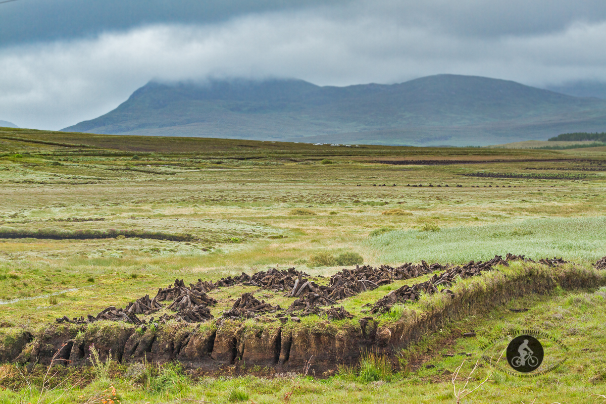 Turf drying on a raised platform with mountaiuns in the background - County Galway