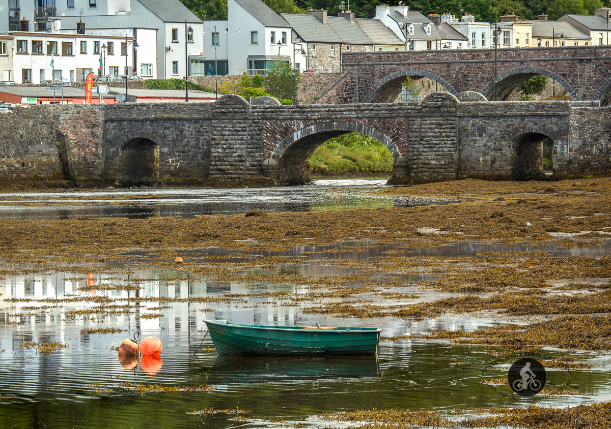 Fishing boat floating in front of bridge and Newport Aquaduct over Newport river - County Mayo - 2