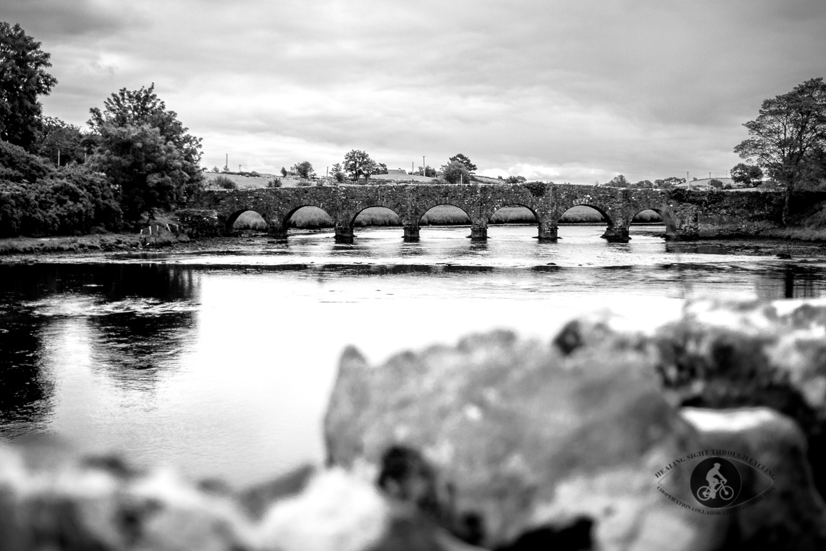 7 arch bridge with blurred rocks in front over Lough Feeagh - County Mayo - Vignette - BW