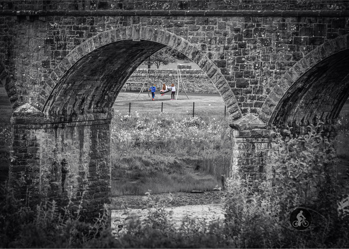 Children playing in Newport community playground seen under Newton Viaduct arch - County Mayo - BW selective colour