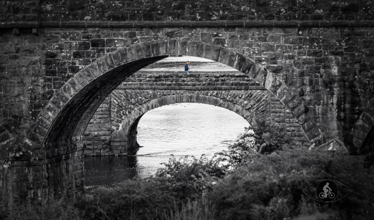 Person walking on bridge over Newtown River under Newton Viaduct arch - County Mayo - BW selective color